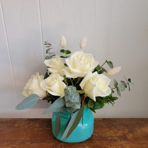 An arrangement of white flowers and eucalyptus leaves in a turquoise mason jar.